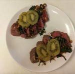 Rare center cut sirloin topped with sauteed spinach, walnuts, and onions served with caramelized kiwi